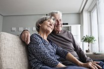 Happy senior couple sitting together on the couch at living room — Stock Photo