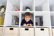 Retrato de menino feliz caucasiano em prateleira — Fotografia de Stock