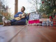 Mann sitzt auf dem Boden und spielt E-Gitarre am Weihnachtsbaum — Stockfoto