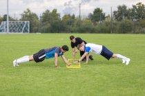 Entrenador haciendo flexiones con jugadores de fútbol en el campo de deportes - foto de stock