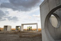 Workers examining concrete structures in rural landscape — Stock Photo
