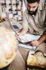 Voyage de planification homme de la maison en utilisant la carte et le carnet — Photo de stock