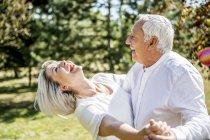Couple de personnes âgées heureux dansant en plein air — Photo de stock