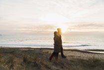 Frankreich, Bretagne, Finistere, Halbinsel Crozon, Paare, die an der Küste bei Sonnenuntergang — Stockfoto