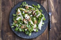 Top view of lettuce with pear, gorgonzola and walnuts on plate — Stock Photo