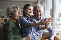 Маленькая девочка принимая selfie с бабушкой и дедушкой в домашних условиях — стоковое фото