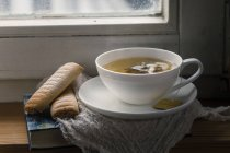 Chamomile tea with book and biscuits on windowbench — Stock Photo