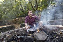 Man cooking at camp fire in forest — Stock Photo