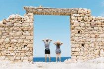 Grecia, Milos, playa de Firopotamos, pareja de pie en puerta en pared de piedra - foto de stock