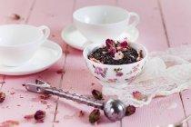 Чаша черного чая с сушеными цветами роз — стоковое фото