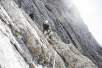 Austria, Tyrol, Wilder Kaiser, two men climbing on via ferrata — Stock Photo