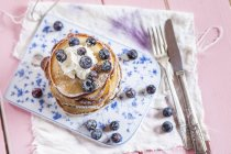 Stack of American pancakes with whipped cream and blueberries — Stock Photo