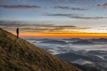 Italia, Umbria, Appennino, escursionista in piedi sul Monte Acuto guardando alba — Foto stock