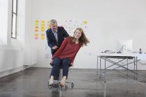 Businessman pushing woman on chair — Stock Photo