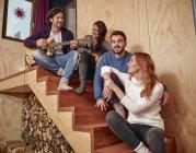 Amigos sentados en escaleras de madera guitarra - foto de stock