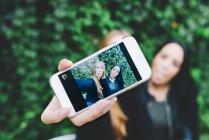 Dos amigos demostrando selfie en teléfono inteligente - foto de stock