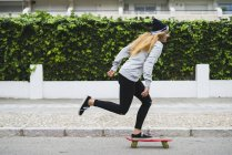Young stylish woman skateboarding on street — Stock Photo