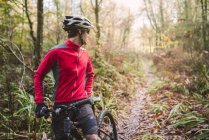 Mountain biker looking back on track in the woods — Stock Photo