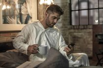 Man sitting on bed looking at phone and drinking coffee — Stock Photo