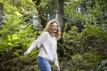 Smiling woman wearing knit pullover walking in nature — Stock Photo