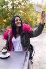 Giovane donna che si fa un selfie in un parco in autunno — Foto stock