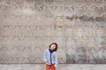 Ragazzino che tira facce buffe davanti al muro di cemento — Foto stock