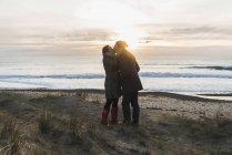 Frankreich, bretagne, finistere, krozonhalbinsel, paar küssen sich am strand bei untergang — Stockfoto
