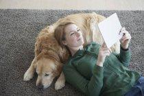 Femme couchée avec chien sur tapis — Photo de stock