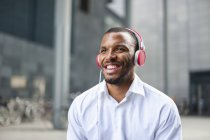 Портрет счастливого бизнесмена, слушающего музыку в наушниках — стоковое фото