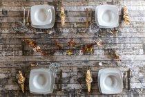 Cuatro ajustes de lugar en la mesa decorada otoñal - foto de stock