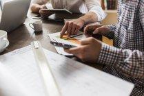 Imagen recortada de colegas en el escritorio con teléfono inteligente, diagrama y plan de construcción - foto de stock