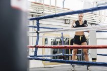 Portrait of confident female boxer in boxing ring — Stock Photo