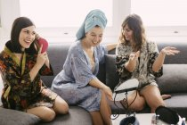 Three young women sitting on the couch wearing bathrobes preparing for the day — Stock Photo