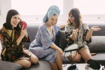 Drei junge Frauen sitzen auf der Couch, Bademäntel, die Vorbereitungen für den Tag tragen — Stockfoto