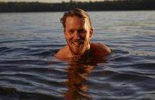 Heureux jeune homme nager dans un lac — Photo de stock
