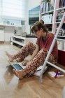 Женщина дома сидит на полу с ноутбуком — стоковое фото
