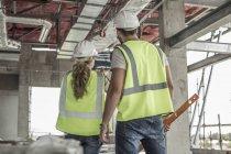 Жінка в захисних спецодягу будівництво працівник та обговорення в будівельному майданчику — стокове фото