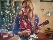 Блондинка женщина играет укулеле перед рождественской елки — стоковое фото