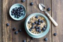 Blueberry muesli en tazón azul sobre madera oscura - foto de stock