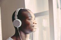 Портрет улыбающегося молодого человека, слушающего музыку в наушниках, глядя в окно — стоковое фото