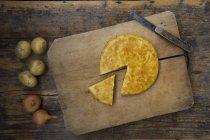 Tranchés en partie tortilla de pommes de terre cuites au four sur une planche de bois avec couteau et pommes de terre fraîches — Photo de stock