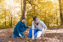 Couple collecting sweet chestnuts in the autumnal forest — Stock Photo