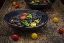 Bowl of Spaghetti al Nero di Seppia with tomatoes and basil leaves on dark wood — Stock Photo