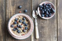 Bowl of blueberry muesli with wolf-berries on dark wood — Stock Photo