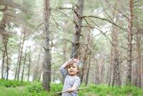 Porträt eines kleinen Jungen mit Holzstab, der im Wald eine Papierkrone trägt — Stockfoto