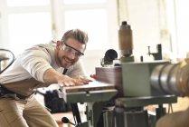 Carpenter using belt sander in his workshop — Stock Photo