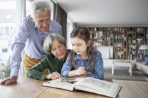 Grandparents watching photo album with their granddaughter at home — Stock Photo