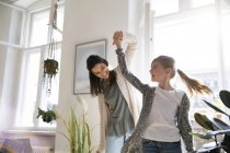 Beautiful caucasian brunette woman dancing with daughter at home — Stock Photo
