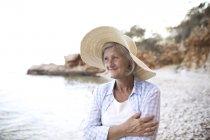 Cheerful senior adult woman in straw hat posing on beach — Stock Photo