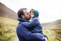 UK, Bala, father and son hugging each other — Stock Photo